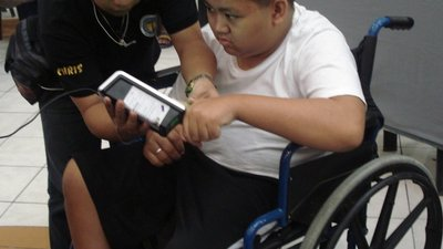 One man using a wheelchair presses his thumb against a small, portable fingerprint scanner. He is looking at something to the side, possibly a computer. The other man holds the scanner, making sure that the thumb is pressed down firmly.