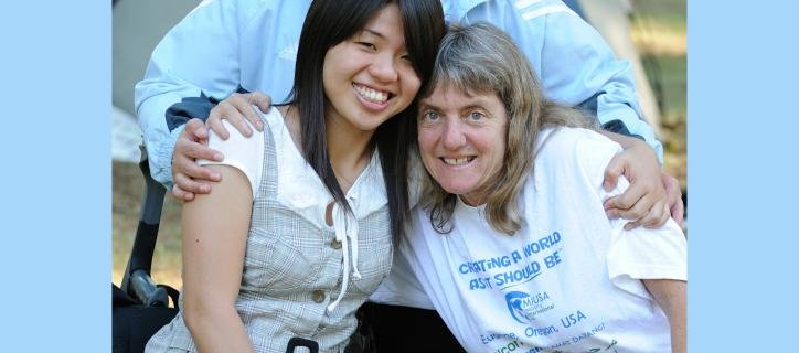 Susan Sygall hugs a young woman with a disability