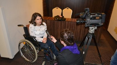 A woman to the left is using a wheelchair and wearing a white shirt and navy trousers. Crouched in front of her is a journalist holding a microphone. There is a video camera recording the interview.
