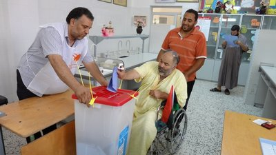In the foreground, there are three men in a polling station. To the left is a poll worker, holding out a secured ballot box. In the middle is a man using a wheelchair and casting his vote. Behind him is a companion observing the voter.