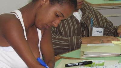 "A young woman writes on a poster in Spanish. The words ""Art. 21"" and ""Art. 39"" can be seen on the poster. The woman has her hair tied back in a bun and is wearing a tank top, which shows that both of her arms end about halfway on the forearm."