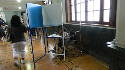 There are several people inside a room with a tile floor and large windows. A woman using a wheelchair is at the polling table, which has a section that is lower and easier for her to access. She reads and writes on her ballot.