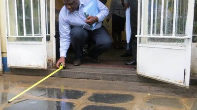 In front of a doorway, a man is crouching down, facing outdoors. Using a tape measure, he is measuring the slope and size of the curb for making recommendations regarding a ramp.