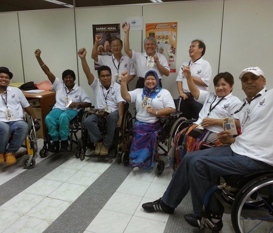 In a room, six men and three women face the camera in a semi-circle. About six people are using wheelchairs. They smile, and most have one arm raised in the air. They are all wearing the white shirts and identification badges of election observers.
