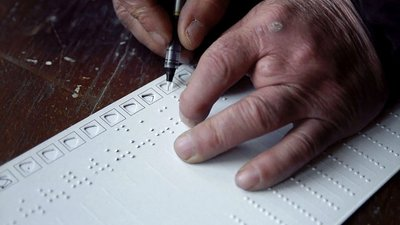 A sheet of long paper with a column of braille writing on the left and a column of small holes on the right, sits on top of a brown desk. The right hand is using a pen to fill in one of the holes. The left hand appears to have four fingers.
