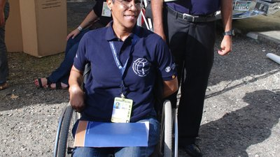 A woman using a wheelchair and wearing a dark blue IFES shirt faces the camera with a smile. A man wearing round sunglasses and a similar dark blue IFES shirt stands behind her. Both are wearing large ID cards that identify them as election observers.