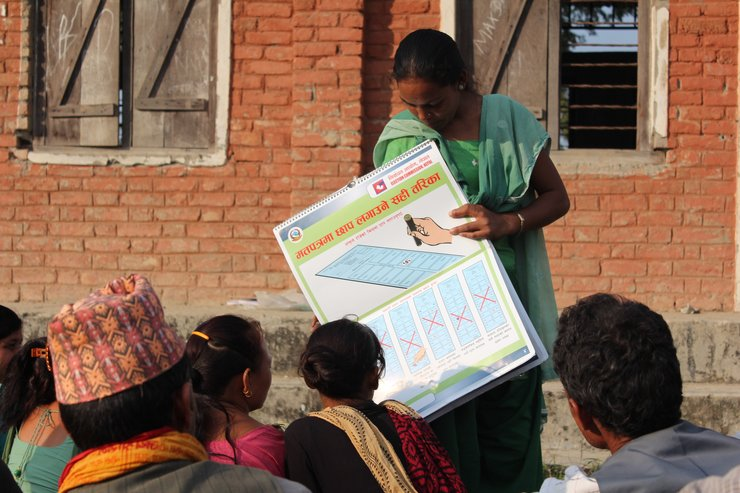 A woman stands in front of a brick wall, holding up a poster written in Nepali and with large illustrations that demonstrates how to mark a ballot correctly. She is the community facilitator. In front of her is a small crowd of people sitting and watching