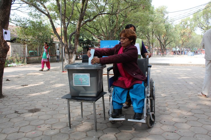 In the center of the photo is a woman using a wheelchair. Next to her is a chair with a plastic ballot box placed on top. The woman is turning slightly to place the ballot inside the ballot box.