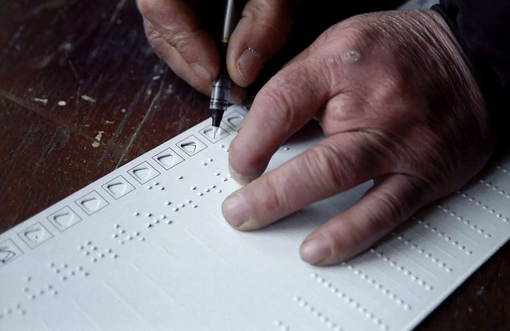 A sheet of long paper with Braille and holes to mark ballots sits on top of a desk. Two hands are poised to fill it out; the left hand appears to have four fingers.