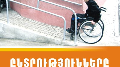 In the poster, a man using a wheelchair is going up a ramp. Above the photo are logos and writing in Georgian.