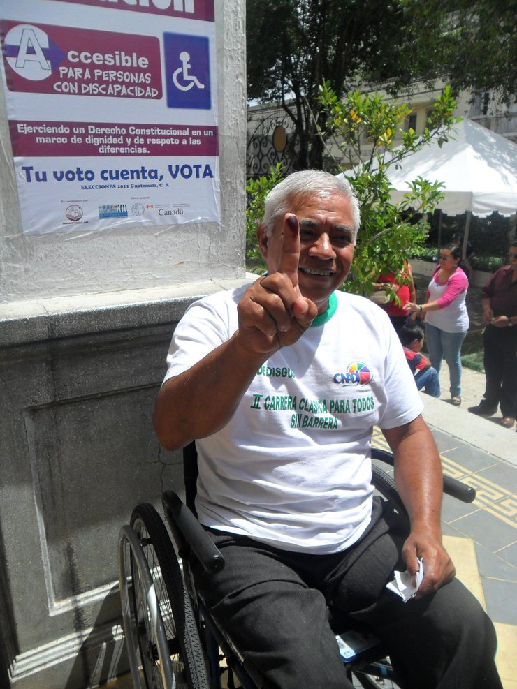 An older man is outside in the sun, smiling and holding up his right index finger, which has black fingerprint ink on the tip. He is using a wheelchair.