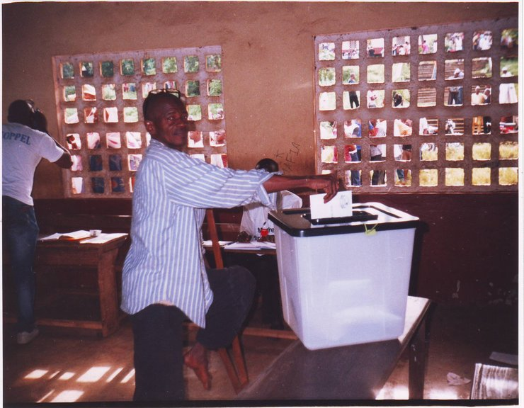 In a dimly lit room, a man using a crutch casts his ballot in the ballot box