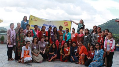 Women with disabilities stand in front of a banner with Nepali writing and smile