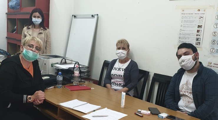 Three women and one man with a disability gather around a table for a group picture. They are wearing masks to protect themselves against the novel coronavirus.