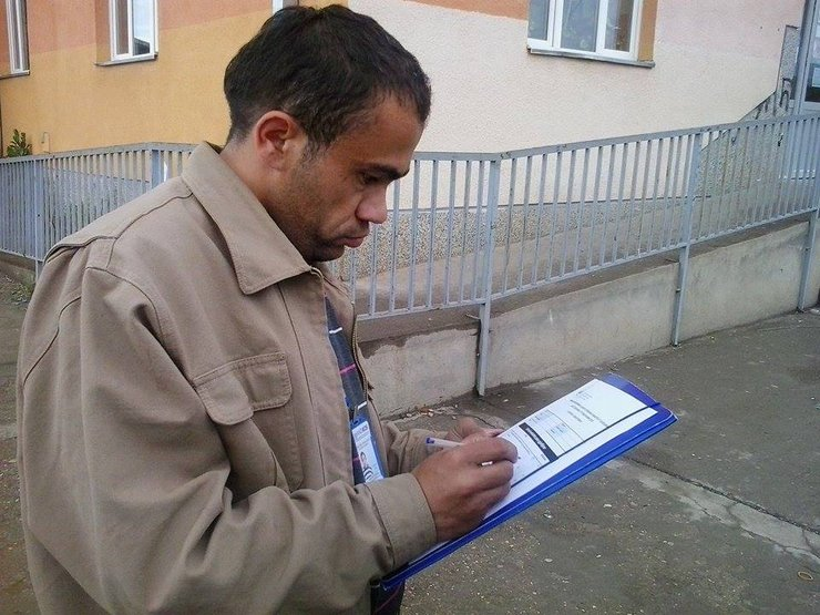 A man wearing a beige coat is outdoors and looking down at a thick clipboard in his hand. He is writing notes.