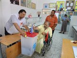A man using a wheelchair deposits his ballot into a ballot box