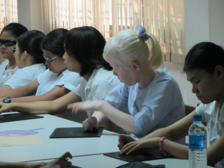 Indoors is a row of six women, all wearing white shirts and sitting at a table. Three women are wearing sunglasses. One woman appears to have albinism. They all seem to be using slates and styluses to write notes in Braille.