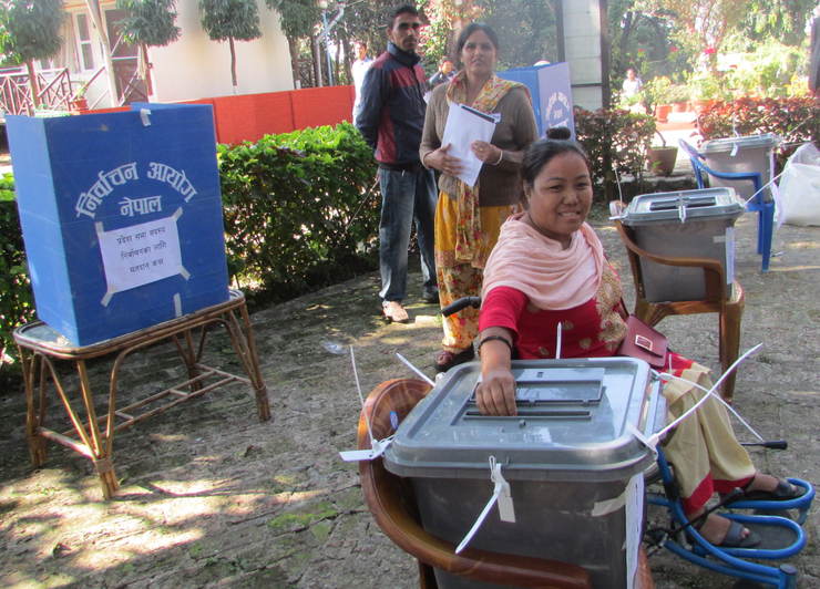 A female wheelchair user places her vote into a ballot box in Nepal