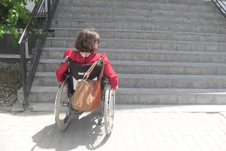 A woman using a wheelchair and wearing a red shirt waits in front of a large staircase.