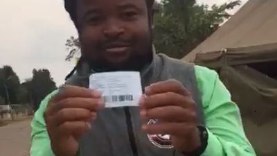 Zimbabwean male stands in front of a tent with his voter registration card