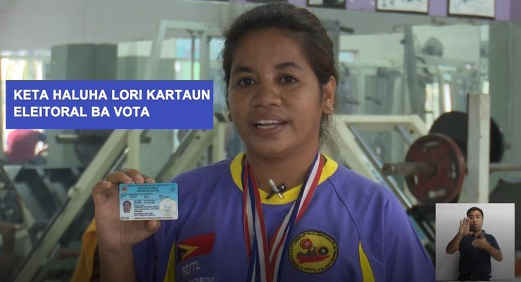 Woman from PSA is holding her ID, a box with a Sign Language interpreter is in the lower right corner