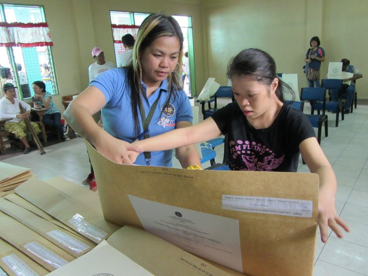 A young women with an intellectual disability casts her ballot in the Philippines