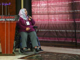 A woman using a wheelchair speaks into a microphone