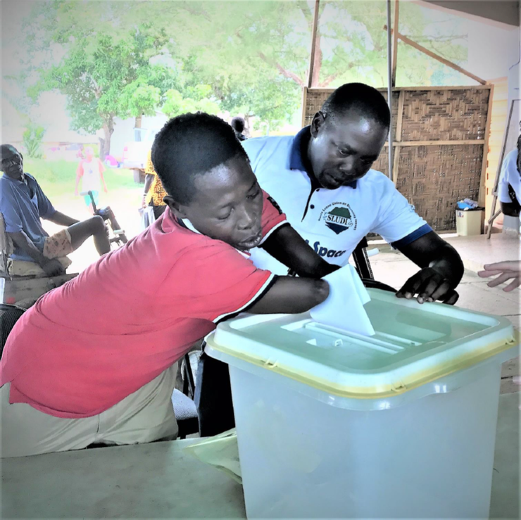 A young man without forearms places his ballot into a ballot box