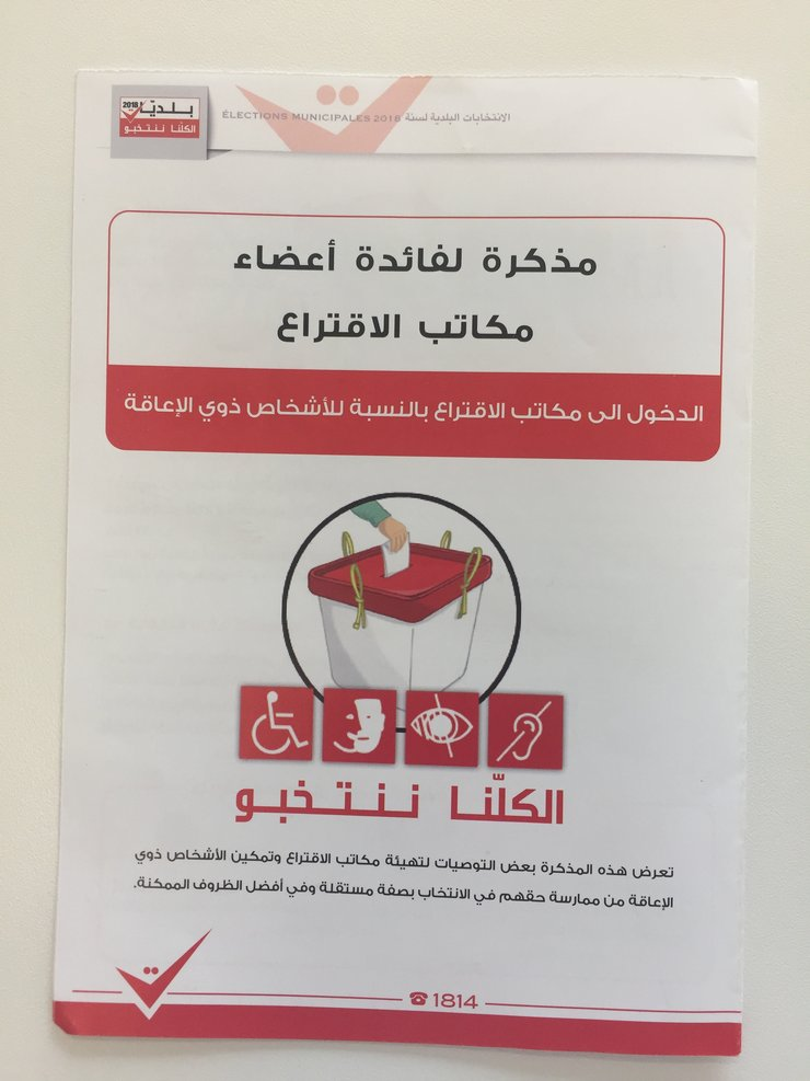 Cover of the pamphlet shows writing in Arabic and a ballot box