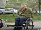 """A screenshot from a video with an image of a man using a wheelchair. On the bottom left side of the screen is an insert with a sign language interpreter and the words """"Today, he is on his way to a polling station"""" appear beside it."""