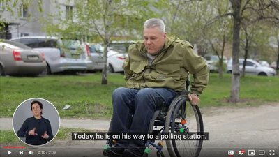 "A screenshot from a video with an image of a man using a wheelchair. On the bottom left side of the screen is an insert with a sign language interpreter and the words ""Today, he is on his way to a polling station"" appear beside it."