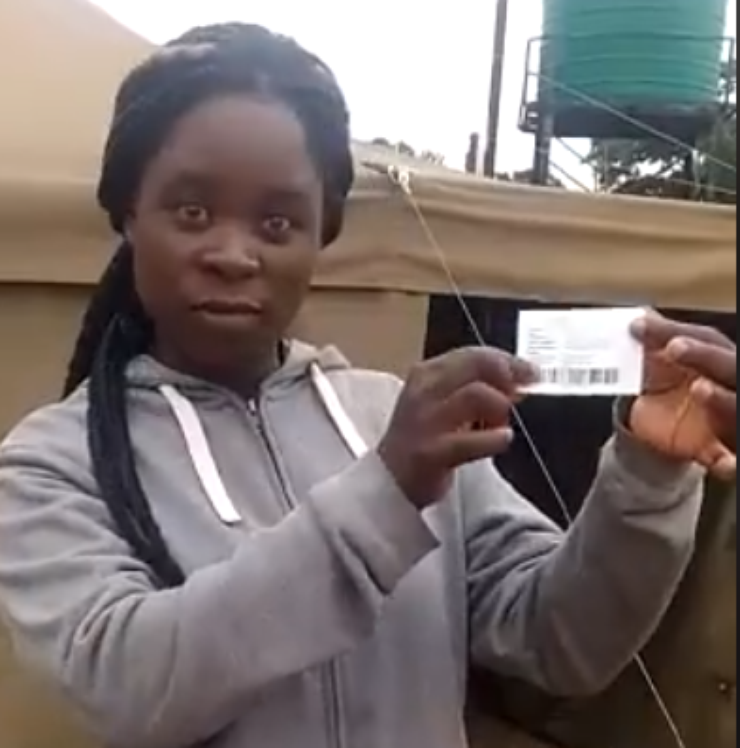 Zimbabwean female stands in front of a tent with her voter registration card