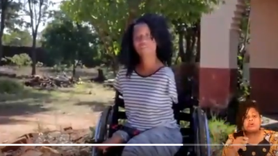 A female wheelchair user faces the camera and a sign language interpreter is on the bottom of the screen