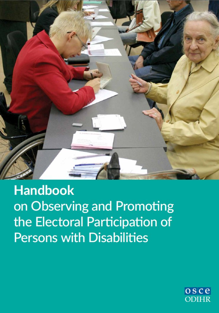 A woman using a wheelchair checks the voter registration of an older voter